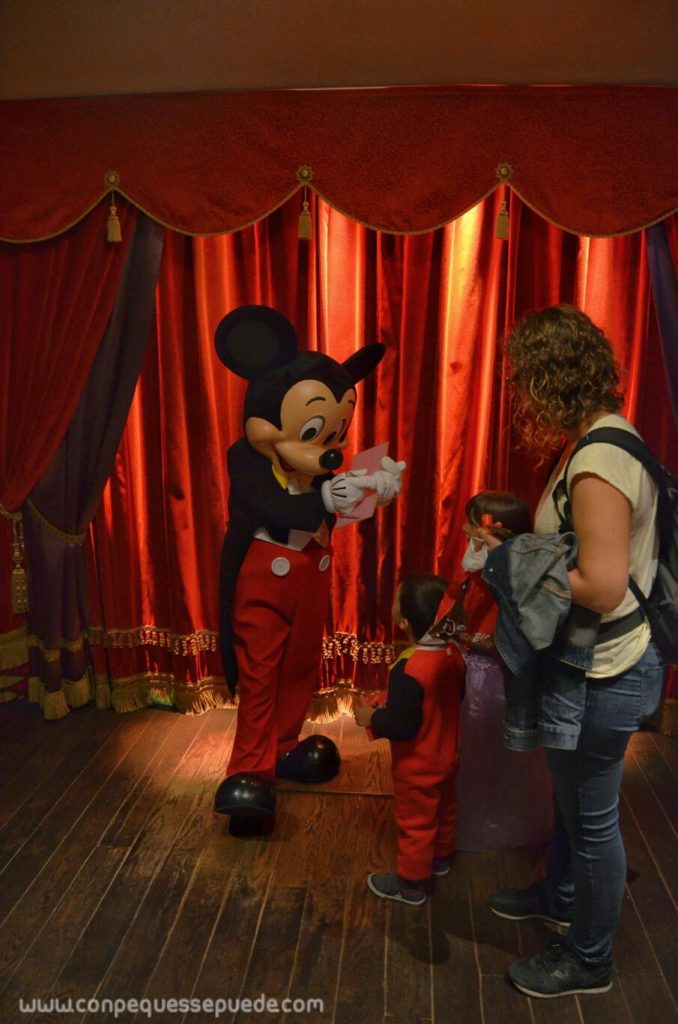 Los peques embobados viendo cómo Mickey firma su libro