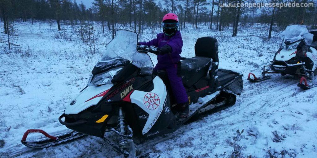 Nuestra hija mayor subida en una moto de nieve de adulto posando.