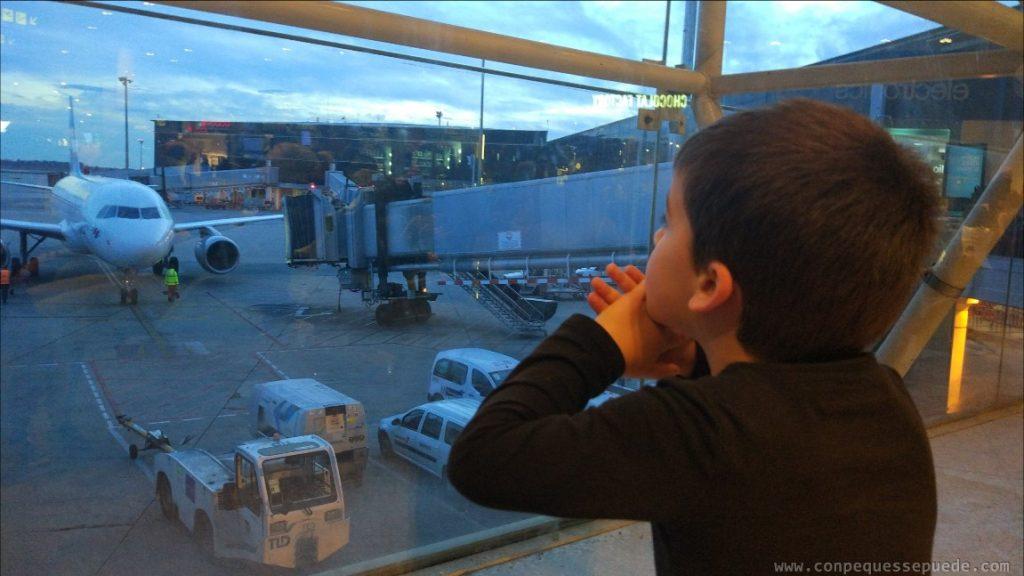 Niño pequeño mirando los aviones en el aeropuerto.